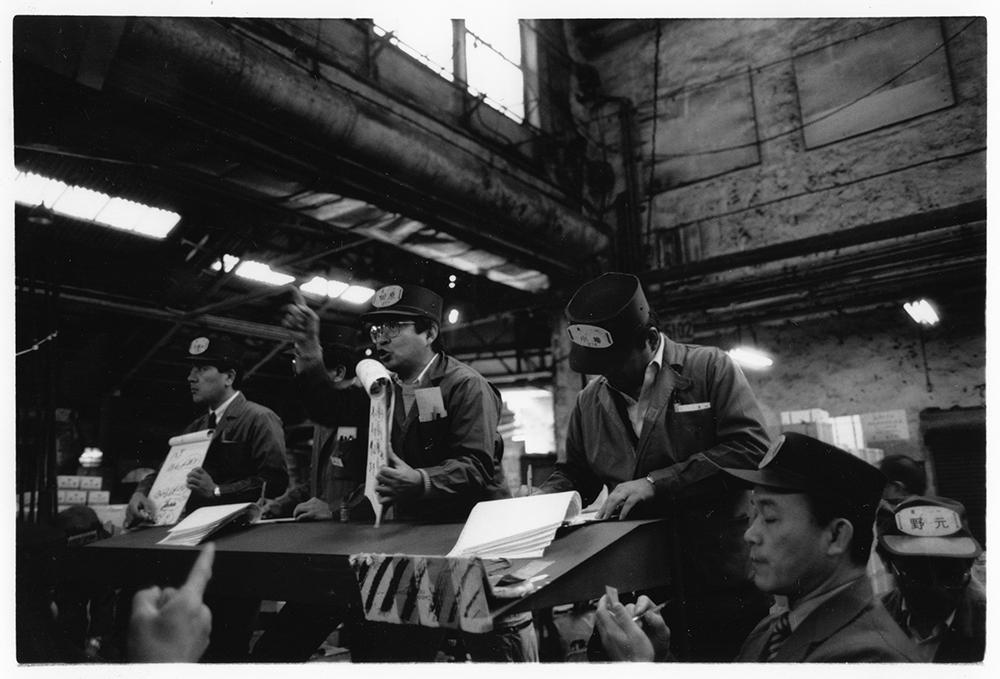 青果卸売会社、トイチ(東一)のセリ人、田原さん。レタスの固定競売で、C級、B級、A級と、下級品から順にセる。手やりを見ながら、買受人のバッジ(帽子)に記された番号(コード番号)をよみ上げる