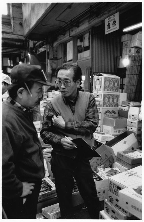 野菜を買い付けに来た小売店主と仲卸(右)。仲卸の店前で、「パセリはチョンガレ」「しいたけチョンブリ」