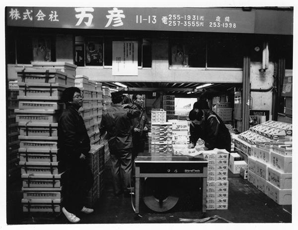 1836年に「万(よろずや)彦兵衛」が創業した果物の仲卸「万彦」の店舗前で。昭和46年ごろまでは「仲買」といっていたが、イメージなどの問題もあり、「仲卸」となった。千疋屋など高級くだものを取り扱う小売店も顧客。